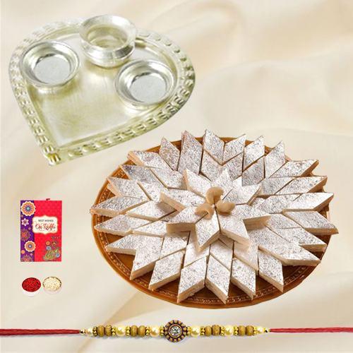 Delicious Kaju Katli and Stylish and Trendy looking Silver Plated Paan Shaped Puja Aarti Thali along Rakhi, Roli, Tilak and Chawal